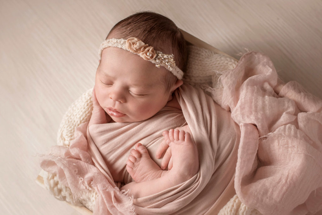 baby girl wrapped in pink fabrics