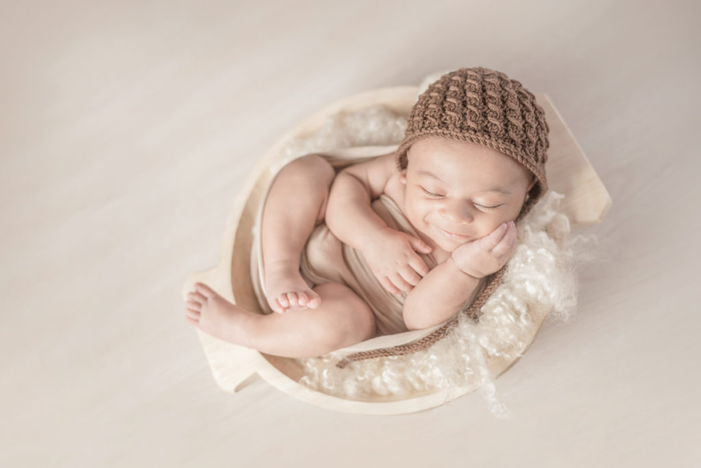 baby smiling in bowl photograph