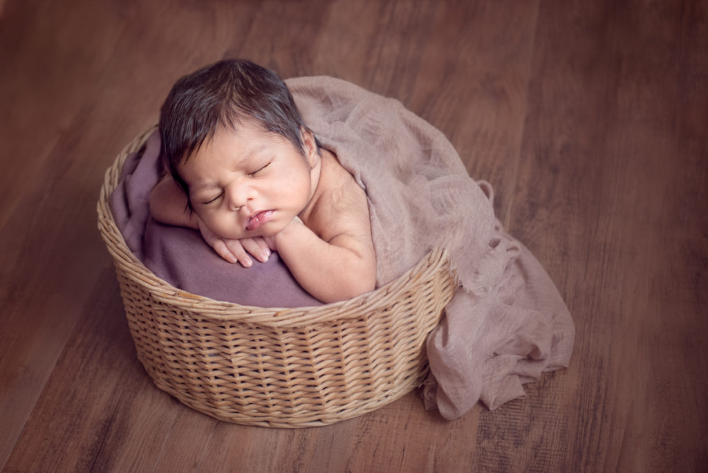 dark moody photo of baby in basket